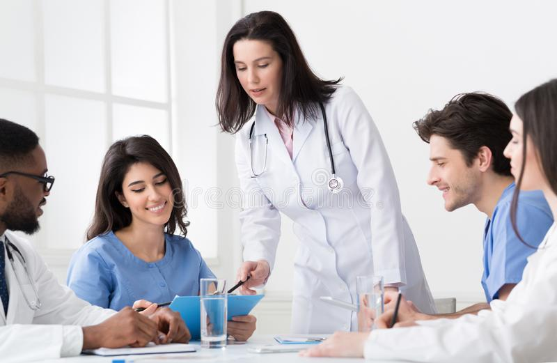 Κύριος γιατρός που συζητά τη διάγνωση με τους οικότροφους και τους επαγγελματίες στοκ εικόνα