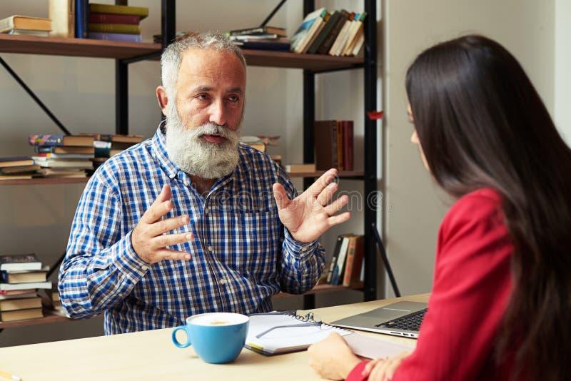 Κύριος εξηγώντας κάτι στο νέο εργαζόμενο στοκ εικόνες