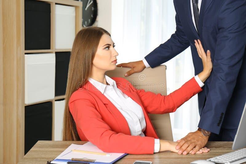 Κύριος κακοποιώντας το θηλυκό γραμματέα του στην αρχή στοκ εικόνα με δικαίωμα ελεύθερης χρήσης
