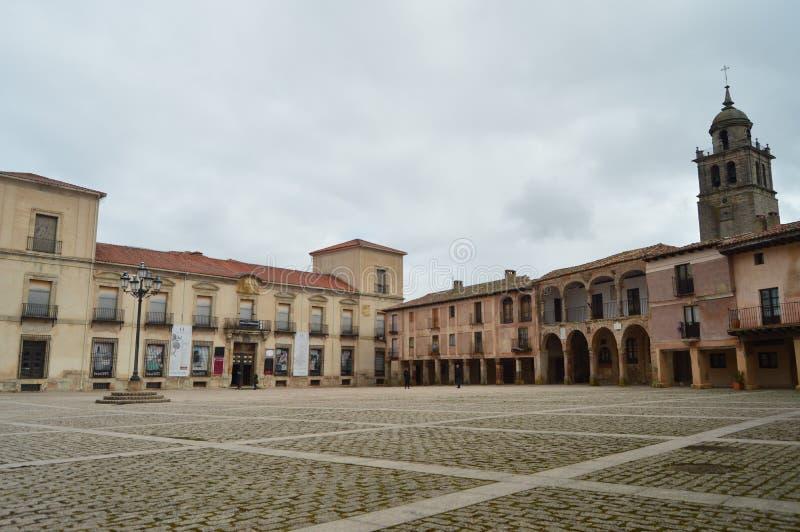 Κύριο τετράγωνο με τις σχηματισμένες αψίδα πύλες κατά την υψηλή άποψη μερών του πύργου εκκλησιών στο χωριό Medinaceli Αρχιτεκτονι στοκ εικόνες