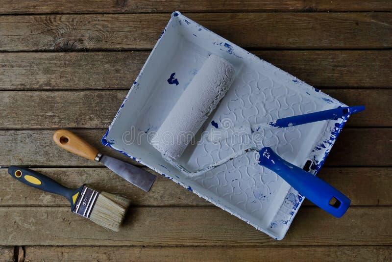 Κύλινδρος και βούρτσα χρωμάτων σε ένα ξύλινο υπόβαθρο στοκ εικόνα