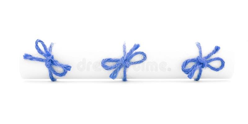 Κύλινδρος της Λευκής Βίβλου που δένεται με τη σειρά, τρεις μπλε κόμβοι που απομονώνονται στοκ εικόνα