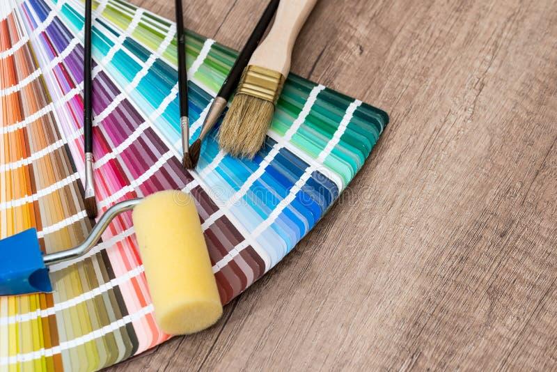 Κύλινδρος χρωμάτων, βούρτσα και κατάλογος δειγμάτων χρώματος σε ξύλινο στοκ φωτογραφίες