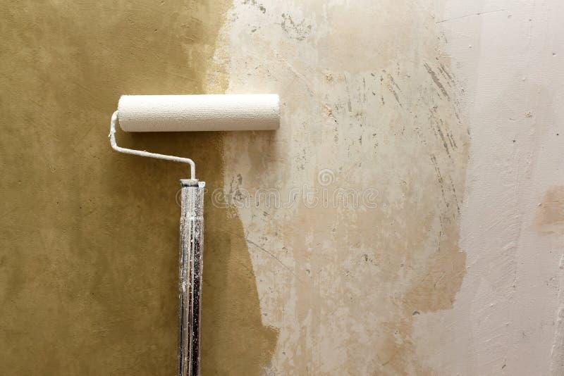 Κύλινδρος χρωμάτων που εφαρμόζει το χρώμα στον άσπρο τοίχο, εγχώριες βελτιώσεις στοκ φωτογραφίες με δικαίωμα ελεύθερης χρήσης