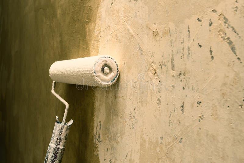 Κύλινδρος χρωμάτων που εφαρμόζει το χρώμα στον άσπρο τοίχο, εγχώριες βελτιώσεις στοκ φωτογραφία με δικαίωμα ελεύθερης χρήσης