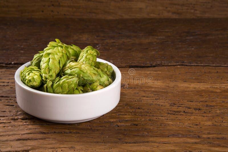 Κώνοι λυκίσκου συστατικών παρασκευής μπύρας στα ξύλινα αυτιά κύπελλων και σίτου στο ξύλινο υπόβαθρο Έννοια ζυθοποιείων μπύρας στοκ φωτογραφίες