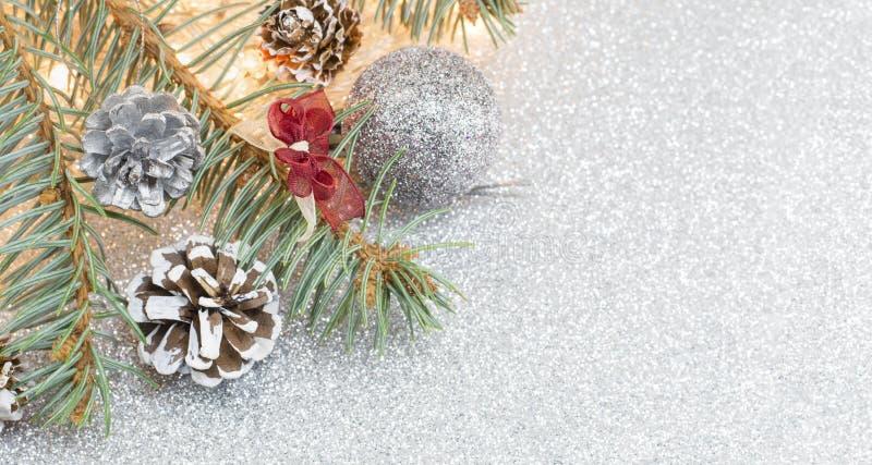 Κώνοι πεύκων και διακοσμήσεις Χριστουγέννων στο λαμπιρίζοντας υπόβαθρο στοκ εικόνα με δικαίωμα ελεύθερης χρήσης