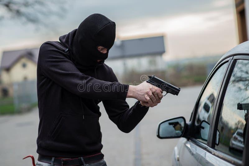 Κλέφτης αυτοκινήτων που δείχνει ένα πυροβόλο όπλο στον οδηγό στοκ εικόνα με δικαίωμα ελεύθερης χρήσης