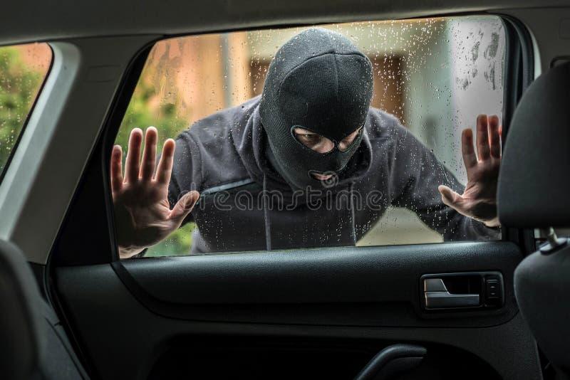 Κλέφτης αυτοκινήτων που κοιτάζει μέσω του παραθύρου αυτοκινήτων στοκ εικόνες