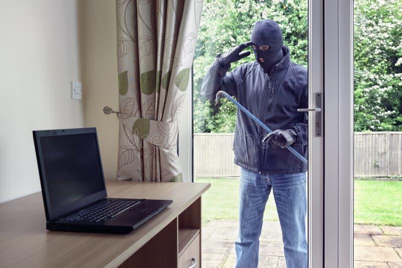 Κλέφτης που κοιτάζει μέσω του παραθύρου πορτών patio σε έναν φορητό προσωπικό υπολογιστή στοκ εικόνες με δικαίωμα ελεύθερης χρήσης