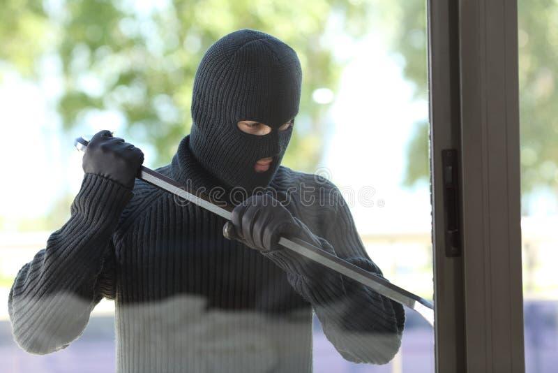 Κλέφτης που προσπαθεί να ανοίξει ένα παράθυρο σπιτιών στοκ εικόνα