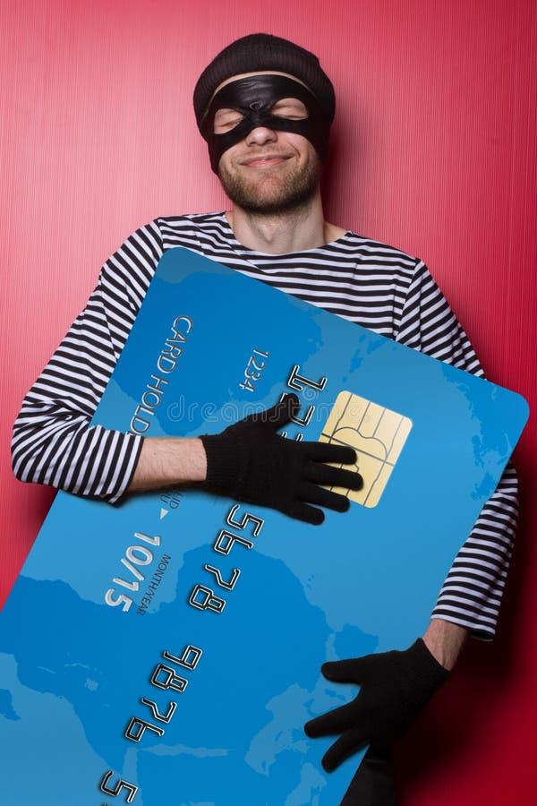 Κλέφτης που χαμογελά με τη μεγάλη μπλε πιστωτική κάρτα στοκ εικόνες