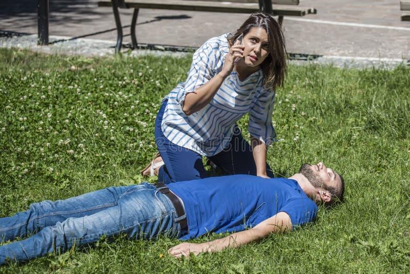 Κλήση έκτακτης ανάγκης για ένα λιποθυμημένο άτομο στοκ εικόνα
