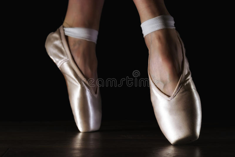 Κλασικά πόδια ballerina ` s κινηματογραφήσεων σε πρώτο πλάνο στα pointes στο μαύρο πάτωμα στοκ εικόνες