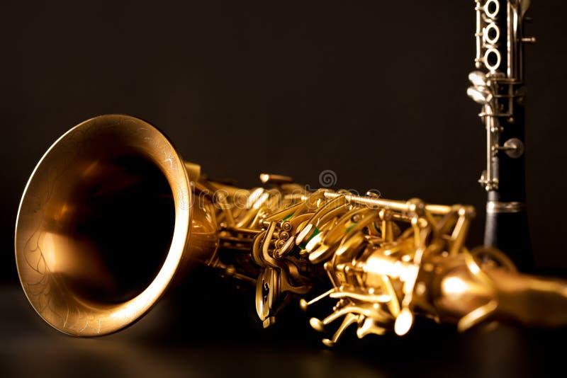 Κλασικά saxophone και κλαρινέτο γενικής ιδέας σκεπάρνι μουσικής στο Μαύρο στοκ φωτογραφίες