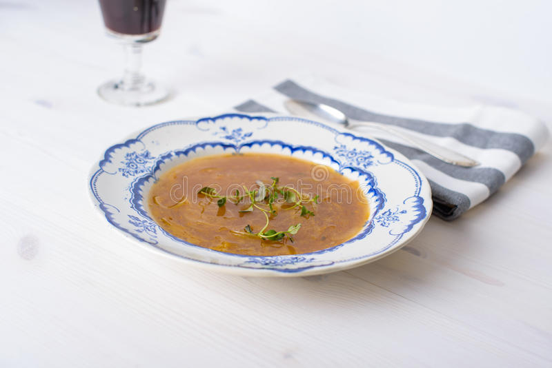 Κλασική γαλλική σούπα κρεμμυδιών σε έναν άσπρο ξύλινο πίνακα με μερικά κόκκινα WI στοκ εικόνα με δικαίωμα ελεύθερης χρήσης