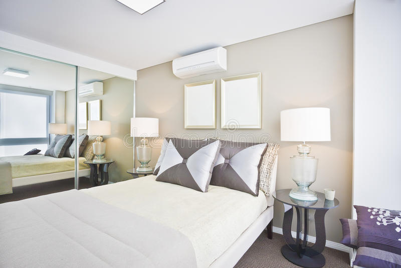Κλασική κρεβατοκάμαρα του σύγχρονου σπιτιού με το άσπρα κρεβάτι και τα μαξιλάρια στοκ φωτογραφία με δικαίωμα ελεύθερης χρήσης