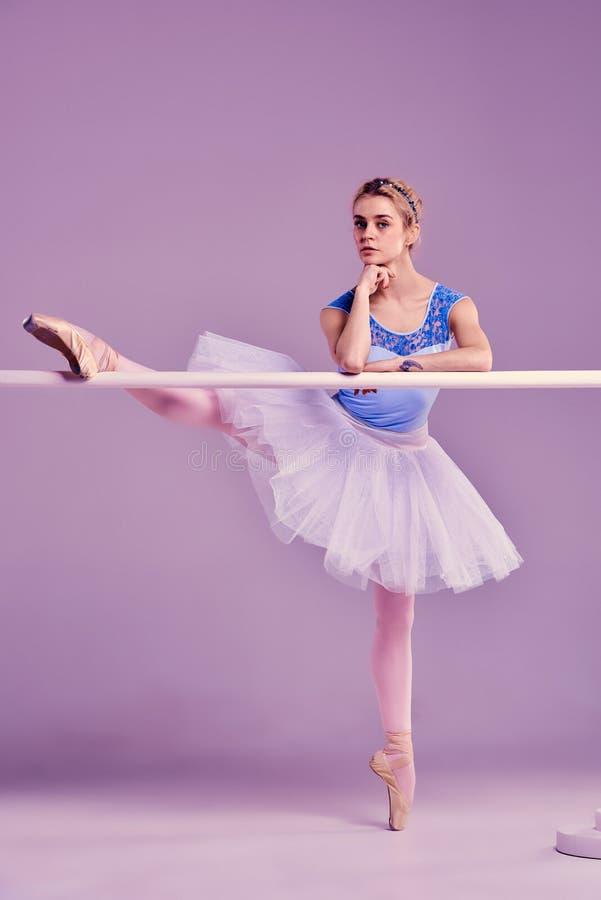 Κλασική τοποθέτηση ballerina στην μπάρα μπαλέτου στοκ εικόνα