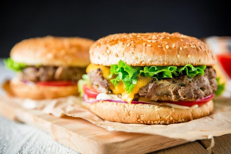 Κλασικό νόστιμο χάμπουργκερ με το νόστιμο βόειο κρέας και σάλτσα στο σκοτεινό υπόβαθρο αμερικανικά τρόφιμα στοκ φωτογραφία με δικαίωμα ελεύθερης χρήσης