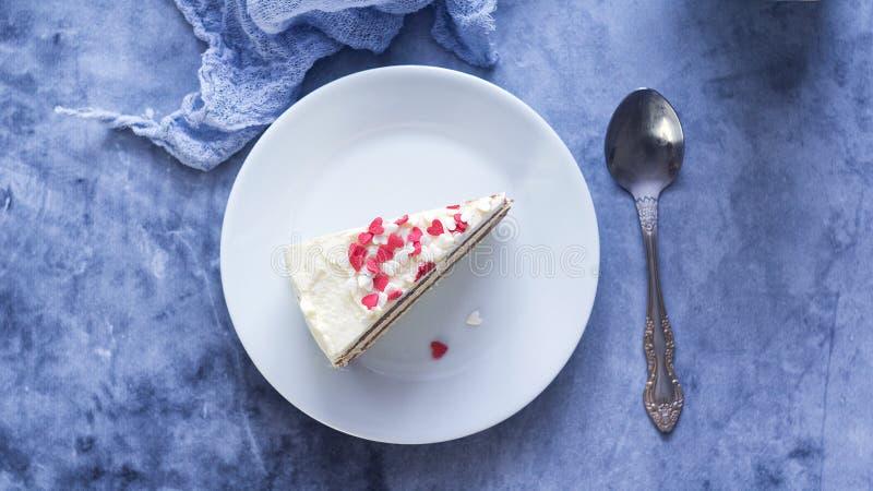 Κλείστε αυξημένος ενός κομματιού ενός κέικ κρέμας στρώματος λεμονιών με τη διαμορφωμένη καρδιά διακόσμηση ημέρας βαλεντίνων στοκ εικόνες
