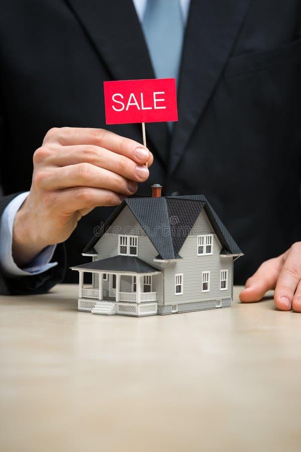 Κλείστε επάνω λίγων σπιτιού και χεριού που κρατούν την ταμπλέτα πώλησης στοκ εικόνα