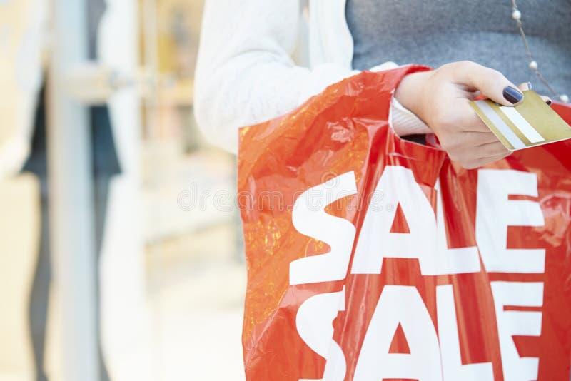 Κλείστε επάνω αγοραστών κάρτας και της τσάντας εκμετάλλευσης της πιστωτικής στη λεωφόρο στοκ εικόνες