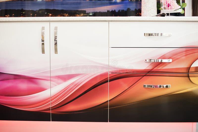 Κλείστε επάνω ενός εσωτερικού κουζινών με τα λευκά και ζωηρόχρωμα γραφεία και λευκά countertops Λεπτομέρεια του άσπρου συρταριού στοκ εικόνα