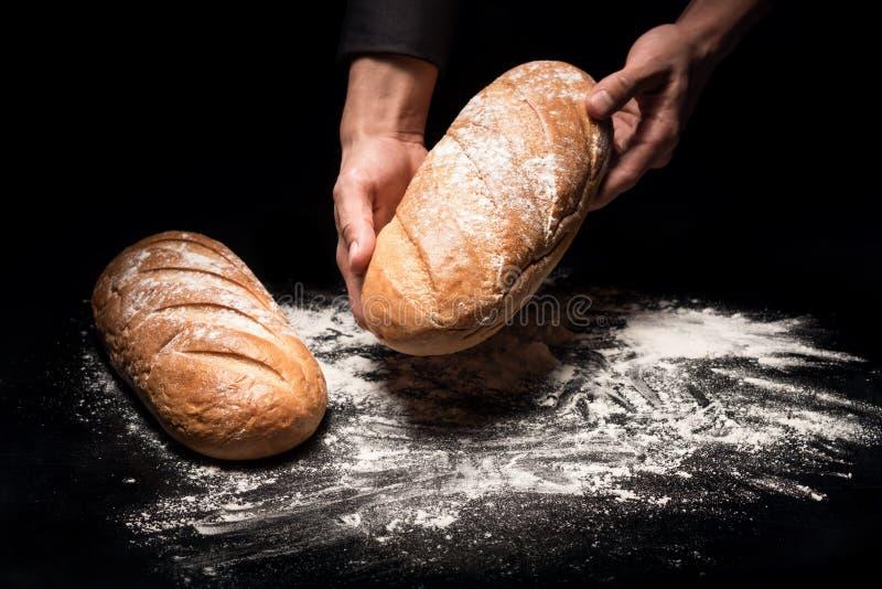 Κλείστε επάνω επανδρώνει τα χέρια κρατώντας ένα ψωμί στοκ εικόνα με δικαίωμα ελεύθερης χρήσης