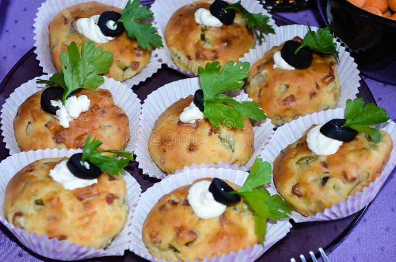 Κλείστε επάνω κατ' οίκον γίνοντα muffins τυριών με τα χορτάρια και τις ελιές στοκ φωτογραφίες