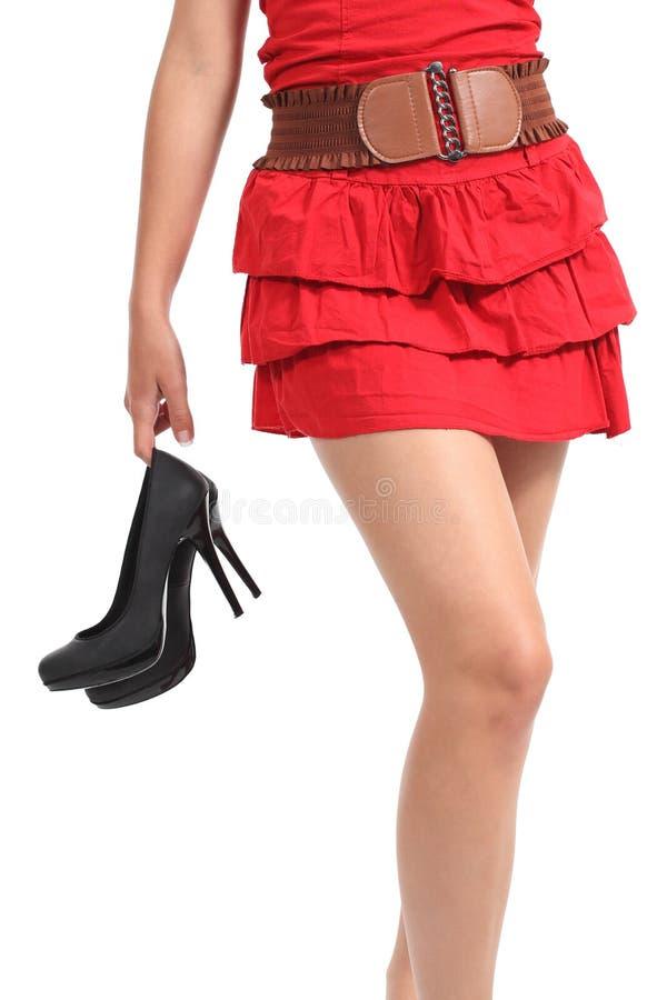 Κλείστε επάνω μιας γυναίκας που περπατά που φέρνει τα τακούνια στο χέρι της στοκ φωτογραφία