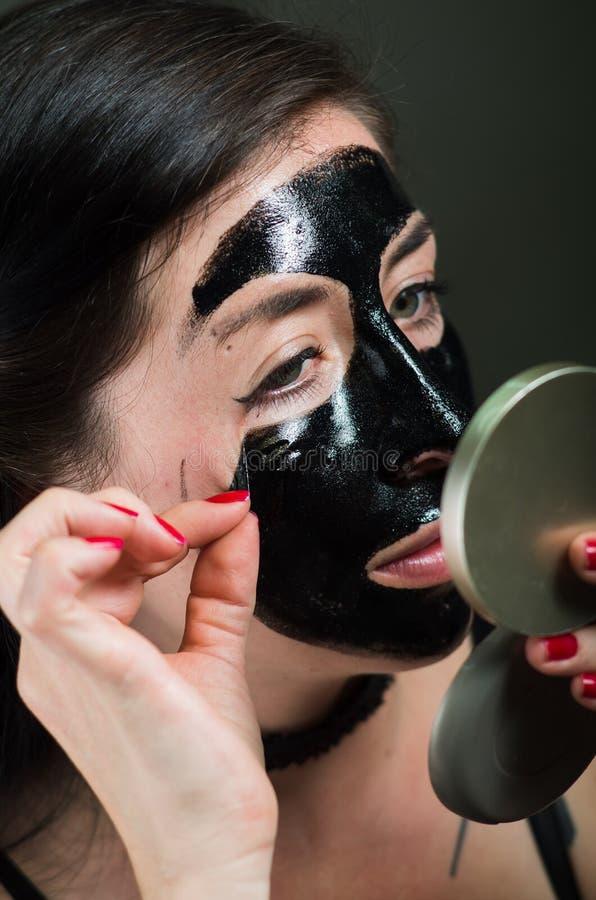 Κλείστε επάνω μιας νέας γυναίκας ομορφιάς που βγάζει τη μισή από μια μαύρη μάσκα προσώπου εξετάζοντας τον καθρέφτη στοκ φωτογραφία με δικαίωμα ελεύθερης χρήσης