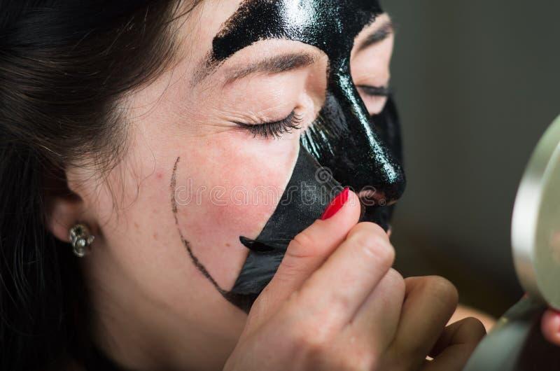 Κλείστε επάνω μιας νέας γυναίκας ομορφιάς που βγάζει τη μισή από μια μαύρη μάσκα προσώπου εξετάζοντας τον καθρέφτη στοκ εικόνες