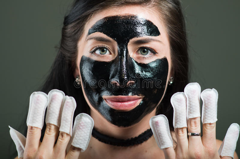 Κλείστε επάνω μιας νέας γυναίκας ομορφιάς χρησιμοποιώντας μια μαύρη μάσκα προσώπου και φορώντας τον προστάτη καρφιών στα καρφιά τ στοκ φωτογραφίες με δικαίωμα ελεύθερης χρήσης
