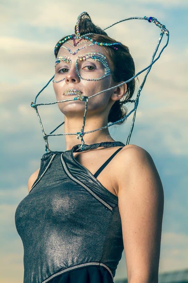 Κλείστε επάνω μιας όμορφης γυναίκας με τα κρύσταλλα που κολλιούνται στο πρόσωπό της στοκ φωτογραφία με δικαίωμα ελεύθερης χρήσης