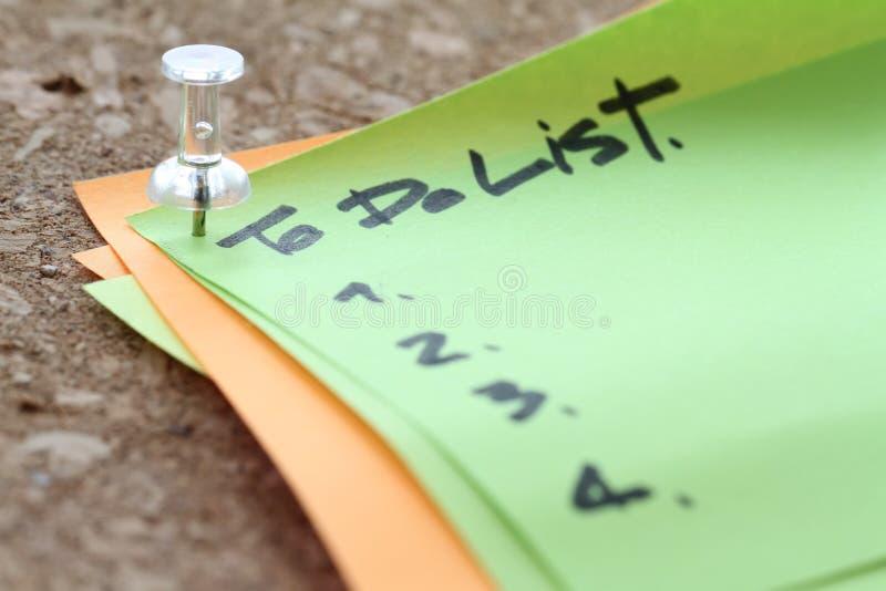 κλείστε επάνω στην καρφίτσα και για να κάνει τη λέξη καταλόγων στην κολλώδη σημείωση με boa φελλού στοκ εικόνες