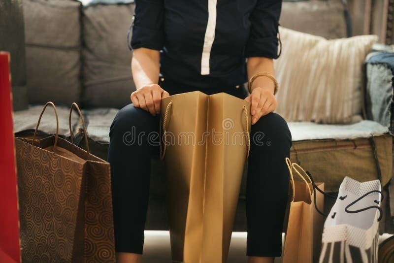 Κλείστε επάνω στην κομψή συνεδρίαση γυναικών στο ντιβάνι με τις τσάντες αγορών στοκ εικόνα