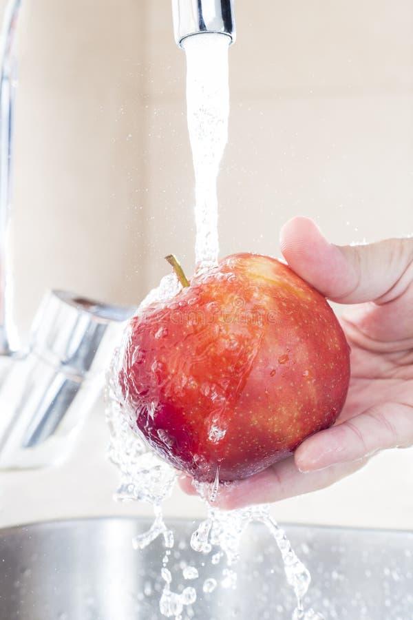 Κλείστε επάνω τα αρσενικά χέρια που πλένουν το μήλο κάτω από το νερό στο νεροχύτη στοκ εικόνα με δικαίωμα ελεύθερης χρήσης