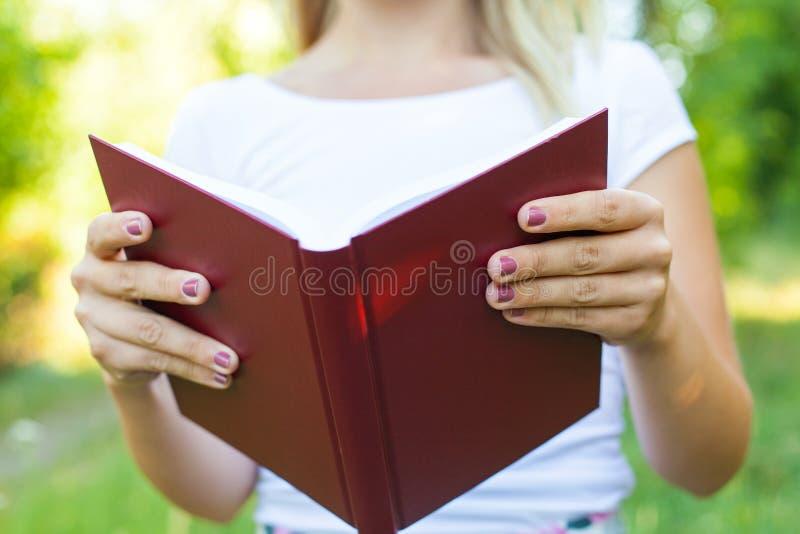 Κλείστε επάνω τα θηλυκά χέρια κρατώντας ένα βιβλίο στοκ φωτογραφίες