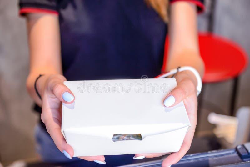 Κλείστε επάνω τα θηλυκά χέρια κρατώντας και δίνοντας πάρτε έξω τα τρόφιμα στο κιβώτιο της Λευκής Βίβλου μέσω του παραθύρου της έκ στοκ φωτογραφία με δικαίωμα ελεύθερης χρήσης