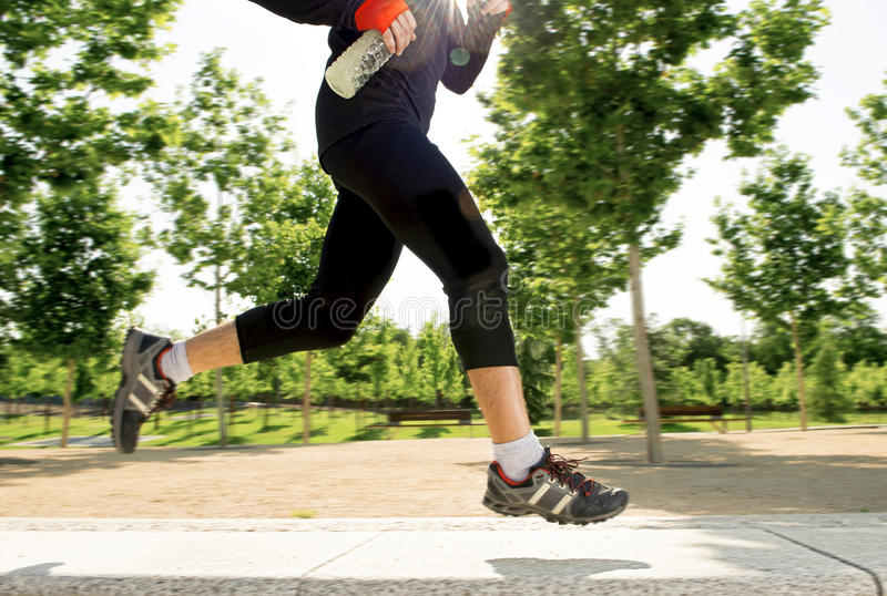 Κλείστε επάνω τα πόδια του νεαρού άνδρα που τρέχει στο πάρκο πόλεων με τα δέντρα έννοια αθλητικού στην υγιή τρόπου ζωής άσκησης π στοκ εικόνες