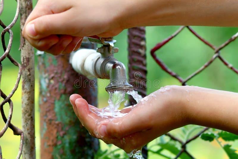 Κλείστε επάνω τα χέρια παιδιών με τις πτώσεις νερού από τον παλαιό ορείχαλκο grunge fauc στοκ φωτογραφία