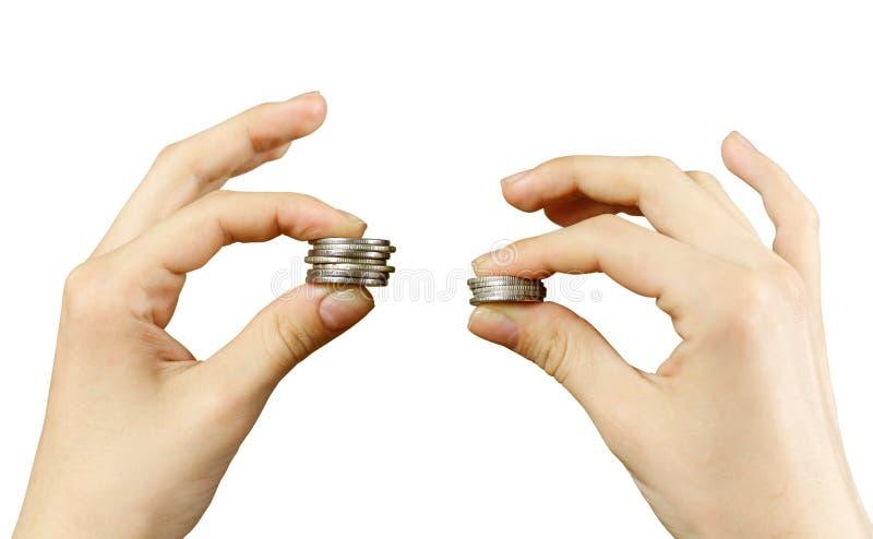 κλείστε επάνω Τα χέρια συγκρίνουν δύο σωρούς των νομισμάτων των διαφορετικών μεγεθών, ι στοκ φωτογραφίες