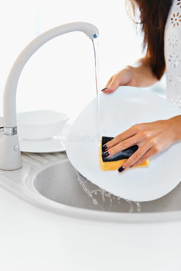 Κλείστε επάνω τα χέρια των πιάτων πλύσης γυναικών στην κουζίνα στοκ εικόνα με δικαίωμα ελεύθερης χρήσης