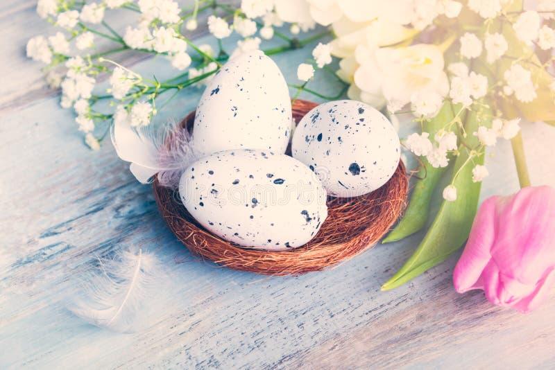 Κλείστε επάνω την άποψη των αυγών Πάσχας στα λουλούδια και τα φτερά φωλιών ανοίξεων πέρα από το μπλε αγροτικό ξύλινο υπόβαθρο στοκ φωτογραφία με δικαίωμα ελεύθερης χρήσης