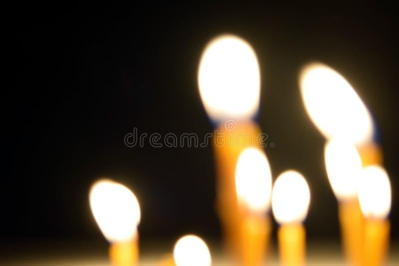 Κλείστε επάνω την άποψη των κεριών που καίνε λαμπρά στο σκοτάδι στοκ εικόνα