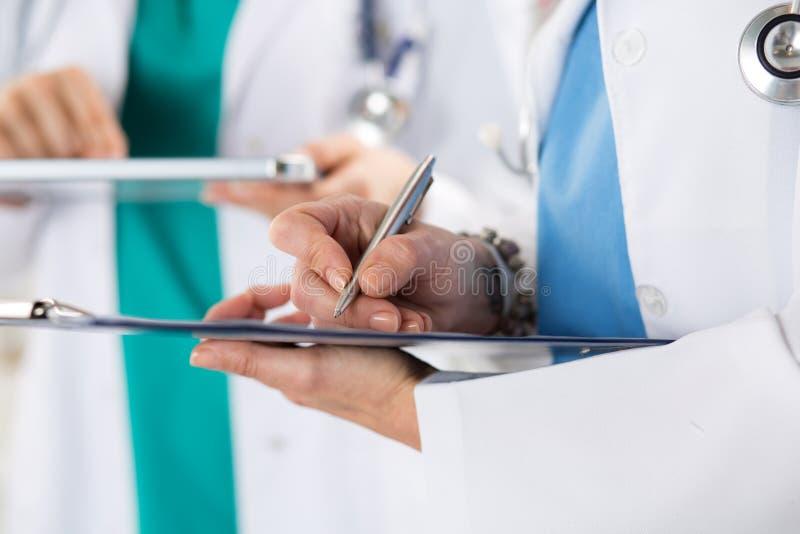 Κλείστε επάνω την άποψη των χεριών ιατρών που κάνει μερικές σημειώσεις στοκ εικόνα
