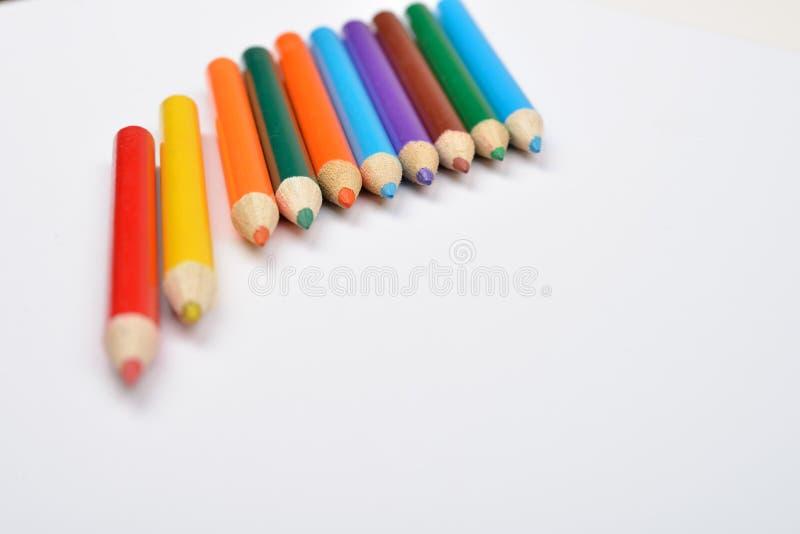 Κλείστε επάνω την εικόνα πολλών μικρών χρωματισμένων κραγιονιών μολυβιών στο λευκό στοκ φωτογραφία