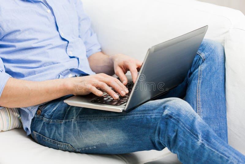 Κλείστε επάνω της δακτυλογράφησης ατόμων στο φορητό προσωπικό υπολογιστή στο σπίτι στοκ φωτογραφία