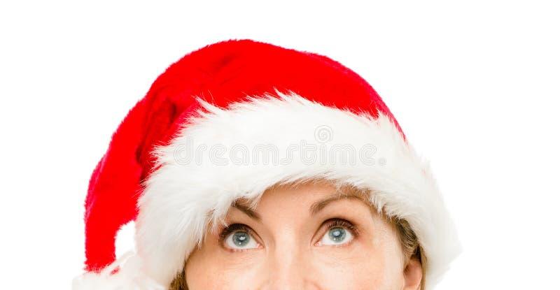 Κλείστε επάνω της αρκετά ώριμης γυναίκας που φορά το καπέλο santa για τα Χριστούγεννα στοκ φωτογραφία