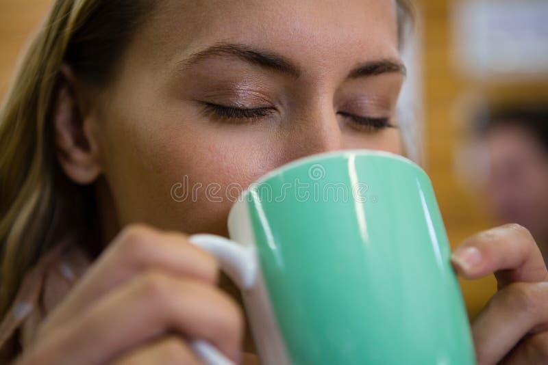Κλείστε επάνω της γυναίκας με κλειστό το μάτια καφέ κατανάλωσης στον καφέ στοκ φωτογραφία με δικαίωμα ελεύθερης χρήσης